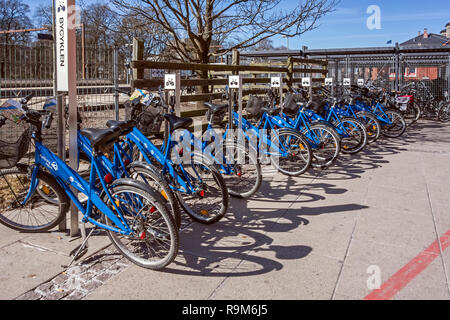 bicycle rack with public bicycles for hire at the railway and bus stations at John F Kennedys Plads Aalborg Jutland Denmark Europe - Stock Image