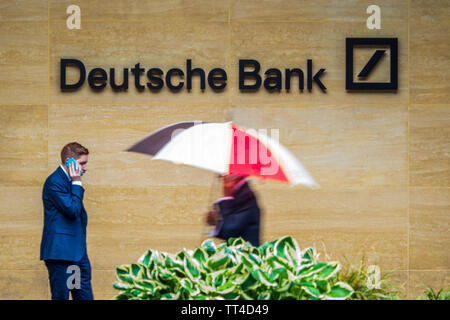 Deutsche Bank London - City workers outside the London offices of Deutsche Bank in the Square Mile in light rain - Stock Image