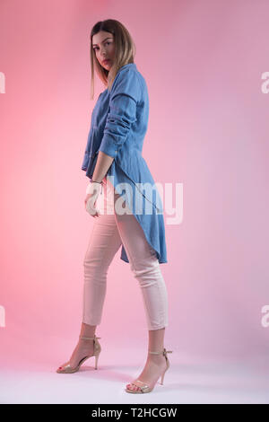 Beautiful young girl posing in studio on pink background. Woman wears blue shirt and high heels on foot. Beauty and fashion concept - Stock Image