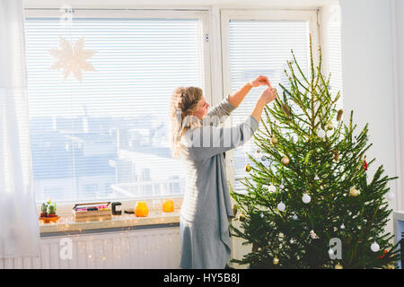 Finland, Helsinki, Woman decorating christmas tree - Stock Image