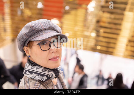 Fashionable Taiwanese woman of Chinese ethnicity in department store looking back at camera - Stock Image