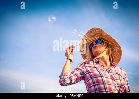 Woman dressed in checked shirt blowing soap bubbles - Stock Image