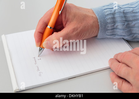 A right-handed senior woman writing a personal letter to a friend using a pad of note paper on a tabletop. England UK - Stock Image
