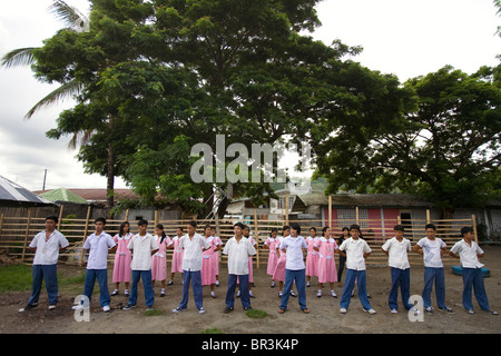 High school students line up in the courtyard at Penaverde Montessori School in Mansalay, Oriental Mindoro, Philippines. - Stock Image