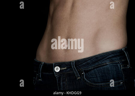Close-up of woman's bare stomach - Stock Image