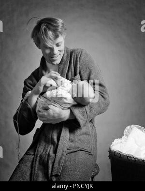 1970s SMILING MAN FATHER FEEDING INFANT DAUGHTER MIDNIGHT BABY BOTTLE - b24785 HAR001 HARS OLD FASHION 1 GIVING FEEDING JUVENILE PEACE TEAMWORK INFANT PLEASED JOY LIFESTYLE FEMALES HEALTHINESS HOME LIFE FULL-LENGTH HALF-LENGTH DAUGHTERS PERSONS INSPIRATION CARING MALES SERENITY FATHERS B&W HAPPINESS CHEERFUL ADVENTURE DADS PRIDE AWAKE SMILES CONNECTION JOYFUL MIDNIGHT BATHROBE JUVENILES MID-ADULT MID-ADULT MAN NIGHTTIME TOGETHERNESS BABY GIRL BLACK AND WHITE CAUCASIAN ETHNICITY HAR001 OLD FASHIONED - Stock Image