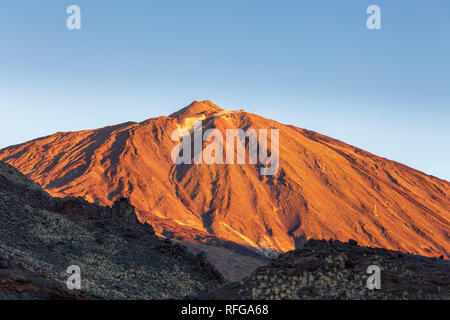 Mount Teide lit up by the first rays of sun at dawn glowing red against a clear blue sky in the Las Canadas del Teide national park, Tenerife, Canary  - Stock Image