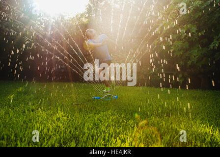 girl playing in the sprinkler - Stock Image