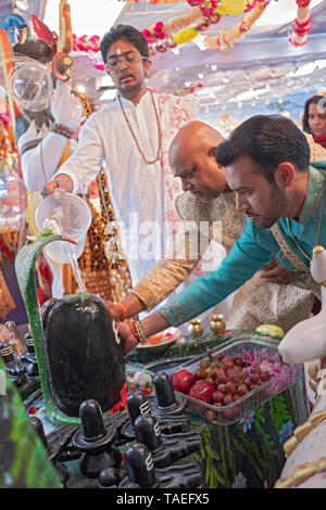 A teenage pandit and two devout worshippers pour water over and touch a Shiva Lingam at a Hindu temple in Jamaica, Queens, New York. - Stock Image
