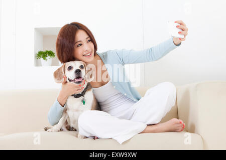 Young woman holding mobile phone and embracing her dog, - Stock Image