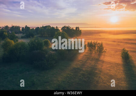 Magnificent dawn with the sun in the fog over the field and forest. Morning summer landscape of Belarus - Stock Image