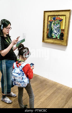 United Kingdom Great Britain England London Southwark Bankside TateModern contemporary art museum gallery interior inside exhibit painting Weeping Woman by Pablo Picasso Asian woman girl mother daughter family audio guide headphones listening - Stock Image