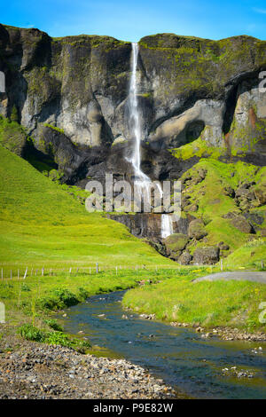 A waterfall and in the foreground a stream in Iceland - Stock Image