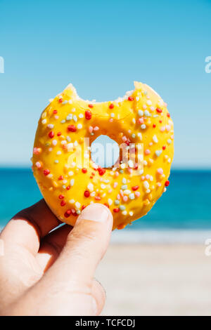 closeup of a nibbled appetizing donut, coated with a yellow frosting and sprinkles of different colors, in the hand of a young man against the blue sk - Stock Image
