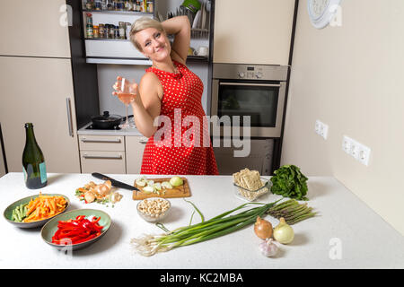 Female holding wine glass in kitchen - Stock Image