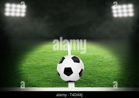 Spotlight on soccer ball in brightly lit outdoor stadium. Focus on foreground and soccer ball with shallow depth of field on background and copy space - Stock Image