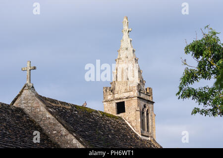 The steeple on All Saints parish church Greater Chalfield with a wood pigeon sitting on the roof below - Stock Image