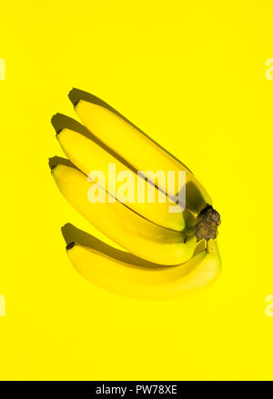Cluster hand of bananas on solid yellow background. Monochrome. Bright sunlight strong shadow. Trendy funky minimalist style. Pop art. Food fashion po - Stock Image