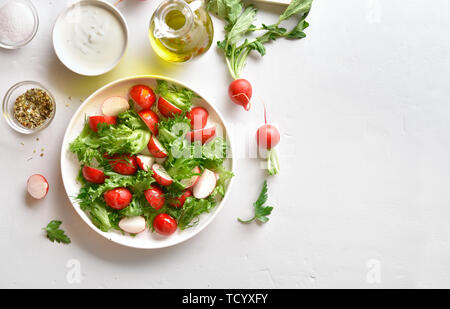 Radish salad with lettuce leaves in bowl over white stone background with copy space. Vitamin spring salad from fresh vegetables.Top view, flat lay - Stock Image