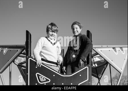 Boy and girl smiling down from the top of a climbing wall in a playground in Daventry, Northamptonshire during the - Stock Image