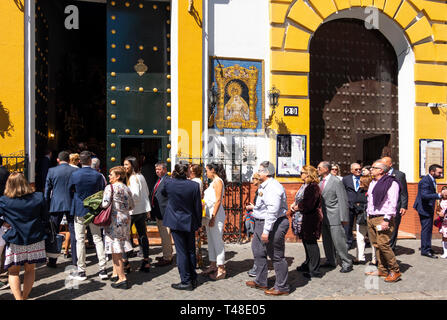People lined up to enter a church to see the ornate altar on Holy Week in Seville - Stock Image