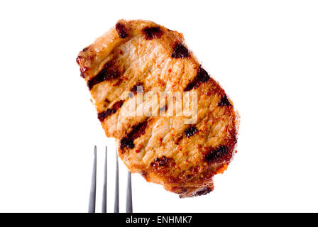 Grilled pork chop without bone on a fork. Spiced with dried chili and paprika. - Stock Image