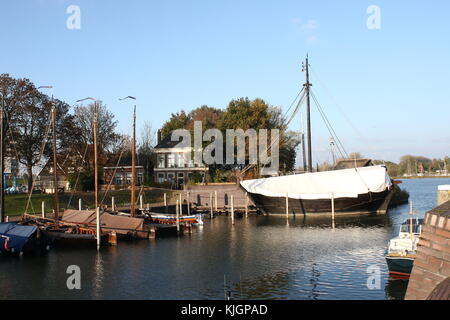 Old harbour of Kampen, Netherlands,  with a replica of  a medieval Cog ship under a tarp, also named The Kampen. - Stock Image