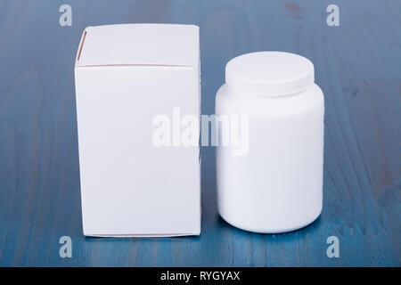 A cardboard box and a white pot on wooden background painted blue. - Stock Image