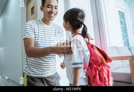 kindergarten student wearing school uniform helped by her father in the morning. back to school preparation - Stock Image