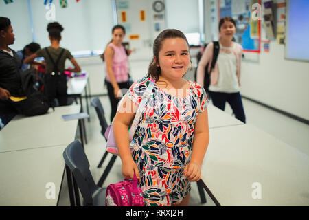 Portrait confident junior high school girl student leaving classroom - Stock Image