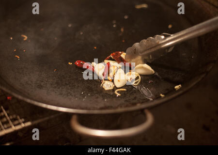 Garlic and red peppers in wok fry pan - Stock Image