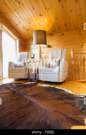 Cream leather reclining chairs with tall wooden base floor lamp and cowhide rug on upstairs floor inside a piece sur piece Eastern white pine log home - Stock Image