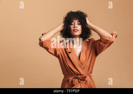 Attractive pretty african woman posing and holding her head while looking at the camera over brown background - Stock Image