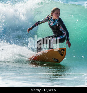 Surfing action as a young teenage female surfer rides a wave at Fistral in Newquay in Cornwall. - Stock Image
