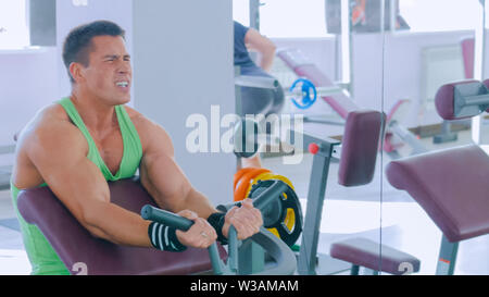 Athletic young man working out on fitness exercise equipment at gym - Stock Image