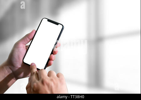 Mockup hands holding mobile phone with blank screen - Stock Image