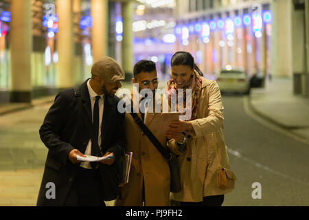 Business people using digital tablet on urban street at night - Stock Image