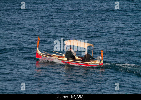 Two tourists crossing Malta's Grand Harbour in a traditional Maltese dghajsa ferry boat or water taxi - Stock Image