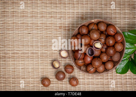macadamia nuts in the bowl on straw (bamboo) background. view from above - Stock Image