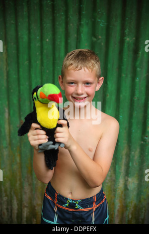 Boy holding toy toucan, Costa Rica - Stock Image