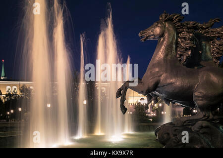 The Four Seasons fountain during night time, containing bronze horse sculptures, Manezhnaya Square, Moscow, Russia. - Stock Image