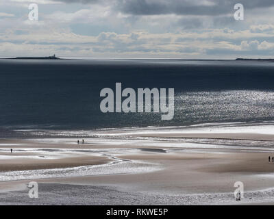 View of the beach at Alnmouth with Coquet Island in distance. - Stock Image
