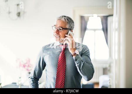 Mature businessman with glasses and smartphone on a business trip standing in a hotel room, making phone call. - Stock Image