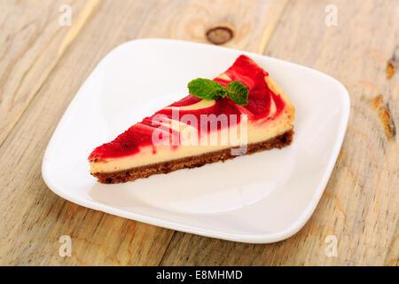 A slice of strawberry swirl cheesecake - Stock Image