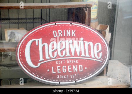 Old Cheerwine sign seen through dirty window in Antique store. Note! Jagged edges on sign are part of the sign, - Stock Image