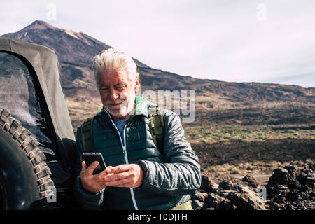 Caucasian old man use modern technology cellular phone at the mountain during trip vacation with off road car at the mountain - planning maps and road - Stock Image