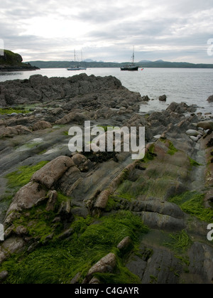 Ridged rocks leading out to sea in the Knoydart area of Scotland. Two sailing boats anchored, Isle of Skye in distance. - Stock Image