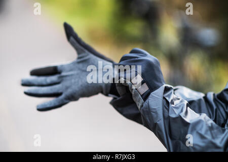 A close-up of a cyclist putting on black gloves outdoors in park. - Stock Image