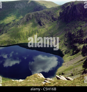 Strong reflections of clouds in the surface of Small Water in the English Lake District - Stock Image