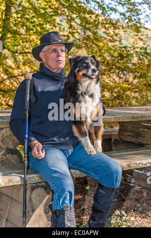 A rambler resting on a bench with his faithful dog - Stock Image